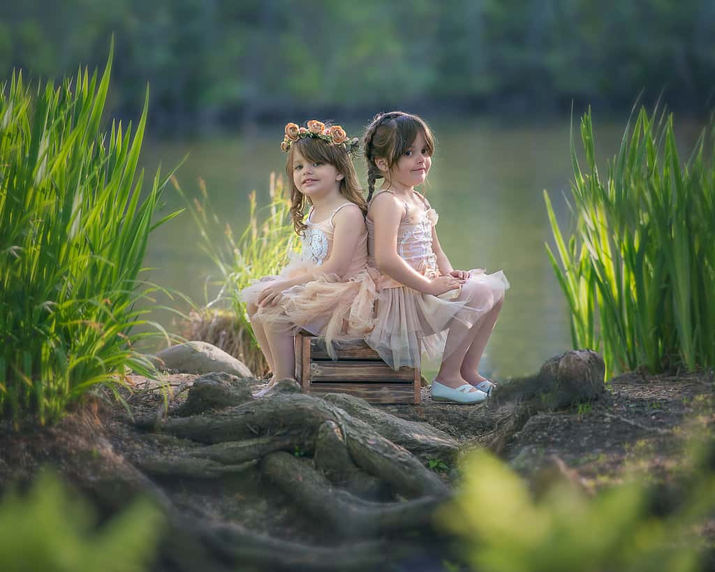 Two little girls with flowers in their hair sitting next to a pond in New York.