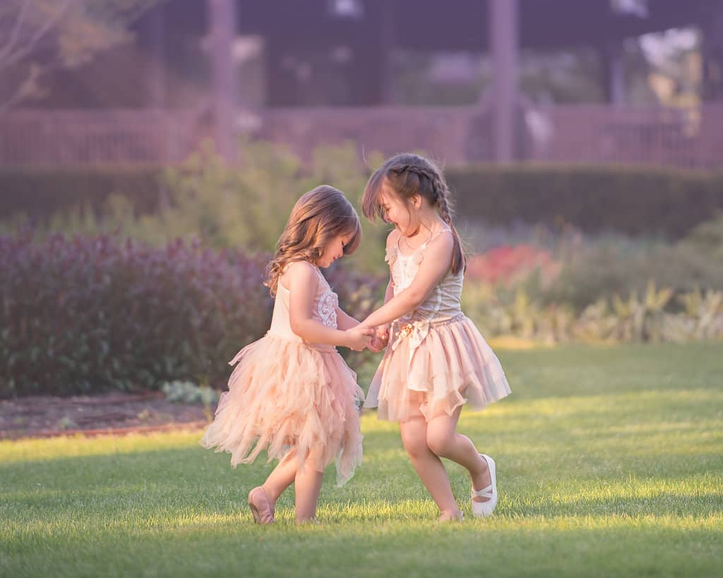 Two little girls twirling in a field in NY with braids in their hair.
