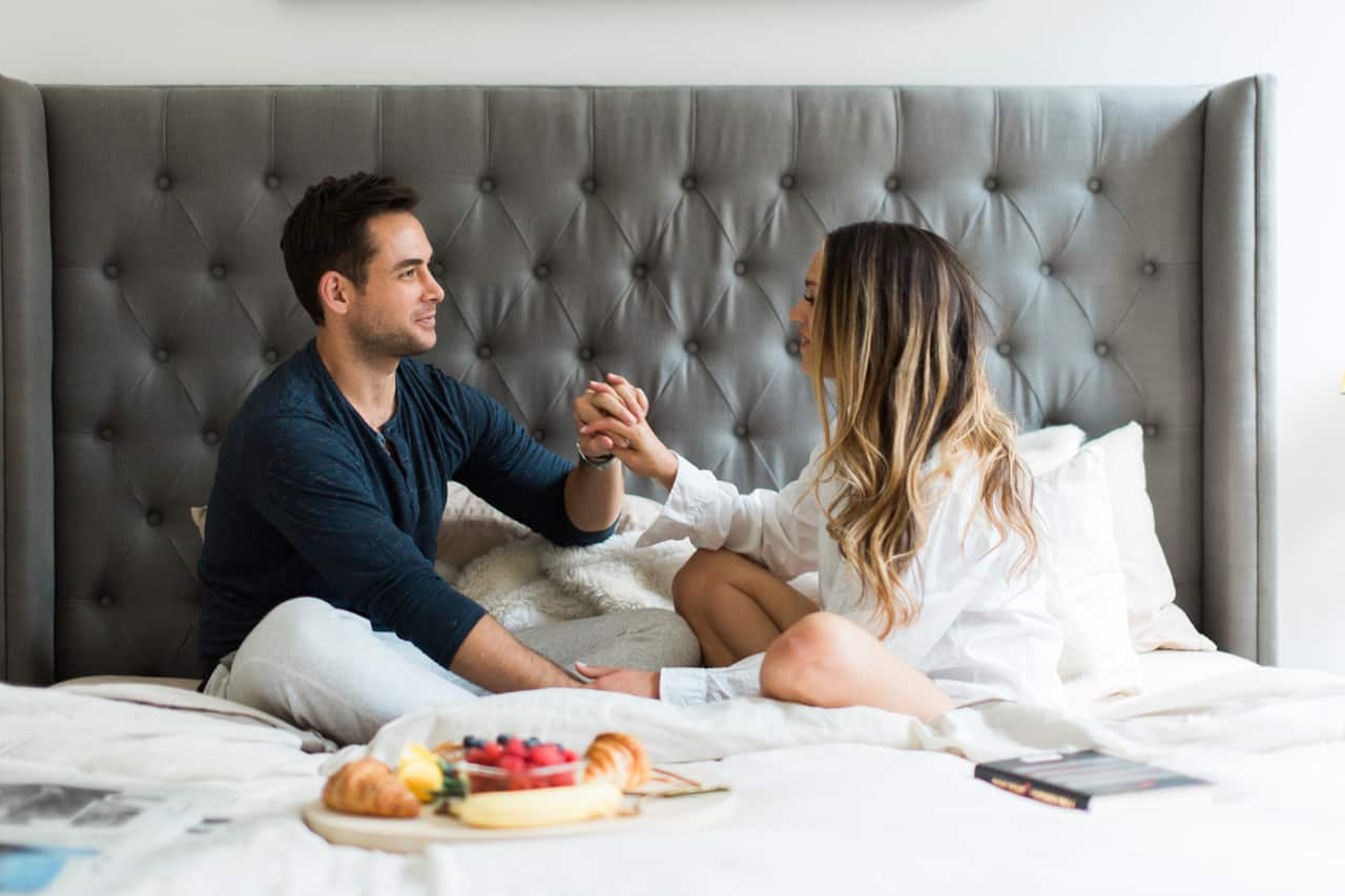 New York couple with perfect hair eating breakfast in bed.