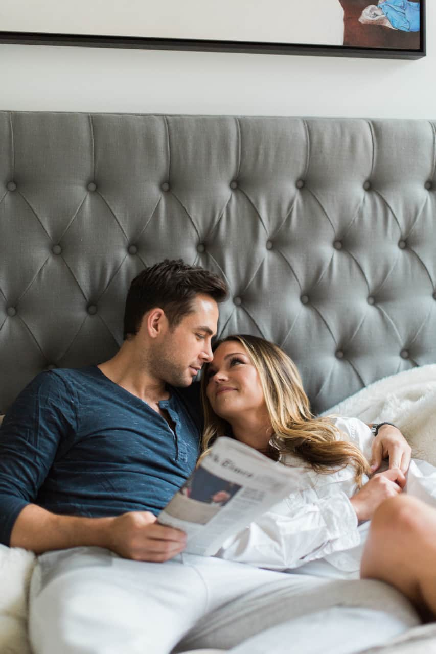 Couple with great hair cuddling in their NYC apartment.