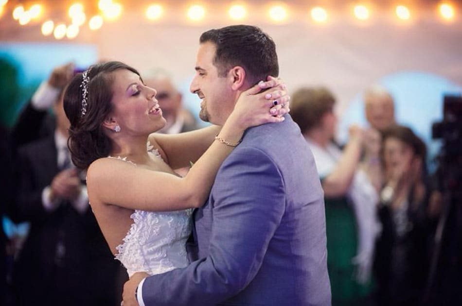 Bride with sparkly headband and curly up-do and groom dancing at their NYC reception under twinkle lights.