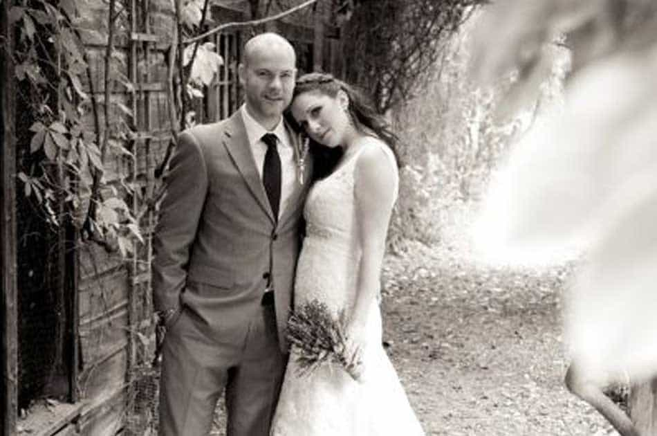Bride with half up half down hair style with braid and groom pose in a grove in NY. Black and white photo.
