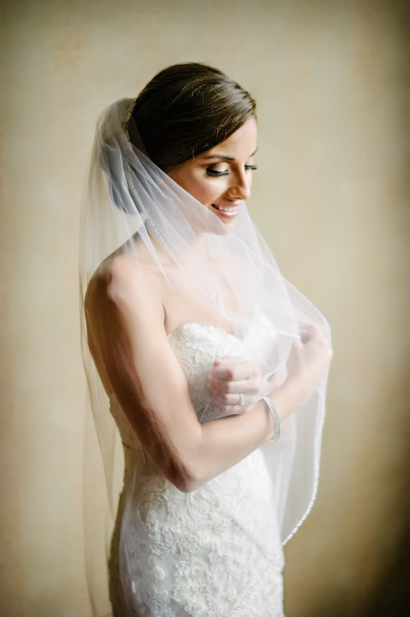 Bride with low knot hairstyle in NY with arms crossed and veil on.