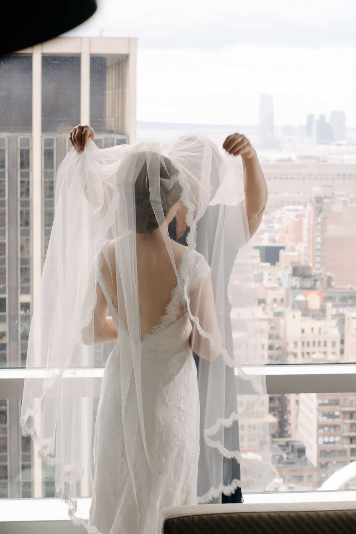Bride with low knot hair style on NY balcony fixing veil.