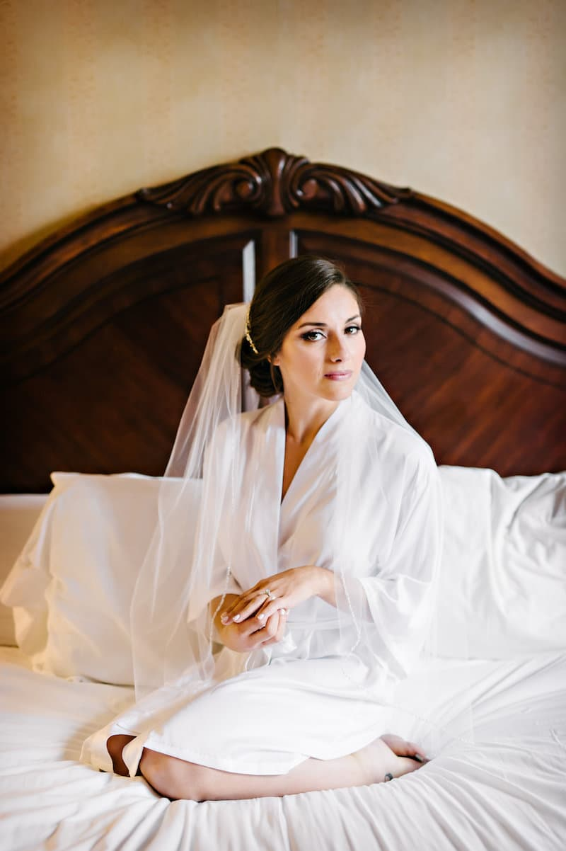 Bride with low knot hair style on bed in New York City wearing a silk robe and veil.
