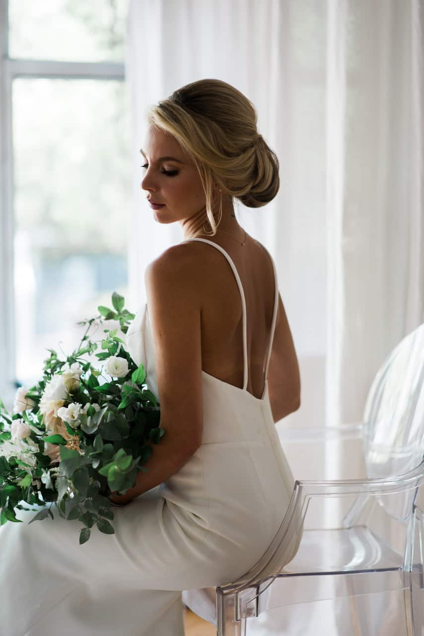 Beautiful bride with her hair up, holding her bouquet in a NY dressing room.
